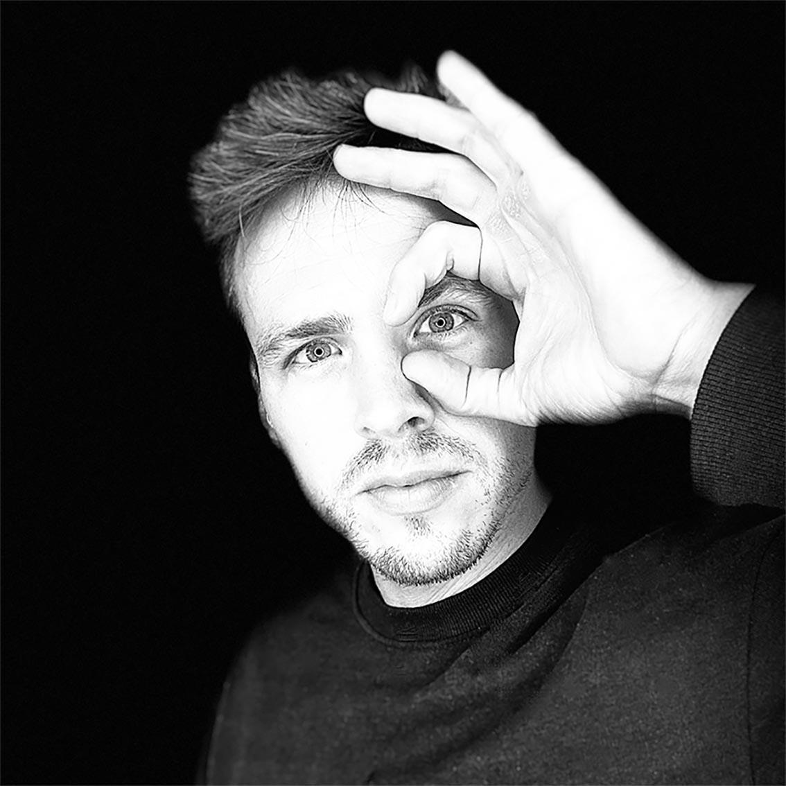 """Dieses Bild zeigt Jakob Fux in Nahaufname mit einer Hand vor dem linken Auge, deren Daumen und Zeige-Finger eine Runde """"Linse"""" formen."""